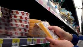 Hombre que selecciona el queso y que lee la etiqueta en colmado almacen de video