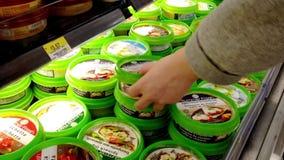 Hombre que selecciona la inmersión de la ensalada dentro de la tienda de Walmart almacen de metraje de vídeo