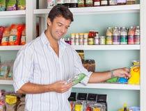 Hombre que selecciona los paquetes de comida en tienda imagen de archivo