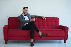 Hombre que sienta y que usa un teléfono elegante fotos de archivo