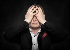 Hombre que siente un dolor de cabeza o que piensa intenso Foto de archivo libre de regalías