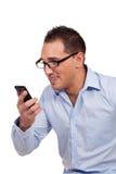 Hombre que sonríe como él lee un mensaje de texto Imágenes de archivo libres de regalías