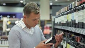 Hombre que sonríe mientras que hace compras para el vino almacen de metraje de vídeo