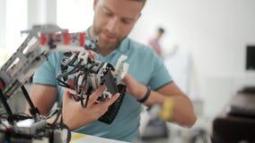 Hombre que sonríe mientras que trabaja en la máquina robótica