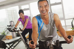 Hombre que sonríe y que ejercita en la bicicleta estática imagen de archivo