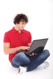 Hombre que sonríe y que trabaja en la computadora portátil Imagen de archivo libre de regalías
