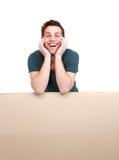Hombre que sonríe y que se inclina en el cartel en blanco Imagen de archivo libre de regalías