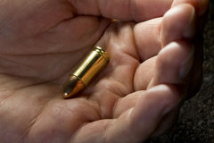 Hombre que sostiene balas disponibles Imagenes de archivo