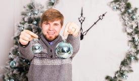 Hombre que sostiene bolas de una Navidad Invierno, partido, concepto del Año Nuevo y de la Navidad Imagen de archivo libre de regalías