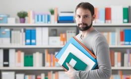 Hombre que sostiene carpetas en la oficina Imagenes de archivo