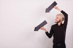 Hombre que sostiene dos flechas que señalan la misma dirección Fotografía de archivo libre de regalías