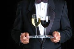 Hombre que sostiene dos vidrios de vino en una bandeja fotos de archivo