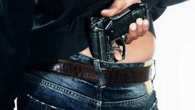 Hombre que sostiene el arma en pantalones metrajes