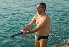 Hombre que sostiene el arpón de la pesca Imágenes de archivo libres de regalías