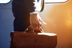 Hombre que sostiene el bolso de cuero mientras que en el tren Fotos de archivo libres de regalías