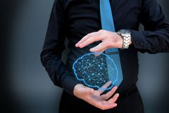 Hombre que sostiene el cerebro poligonal que brilla intensamente en fondo oscuro fotografía de archivo libre de regalías