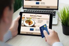 Hombre que sostiene el cuaderno de la tableta de la tarjeta de crédito con la comida de la entrega del app Fotos de archivo