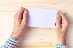 Hombre que sostiene el folleto en blanco como mofa encima del espacio de la copia imagen de archivo