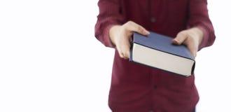 Hombre que sostiene el libro cerrado aislado en blanco Imagen de archivo
