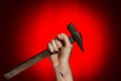 Hombre que sostiene el martillo sobre rojo Fotografía de archivo