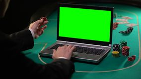 Hombre que sostiene el microprocesador afortunado y que apuesta a servicios de juego en el ordenador portátil, pantalla verde almacen de video