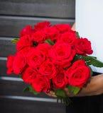 Hombre que sostiene el ramo de rosas rojas Imagenes de archivo