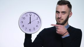 Hombre que sostiene el reloj en fondo blanco aislado metrajes
