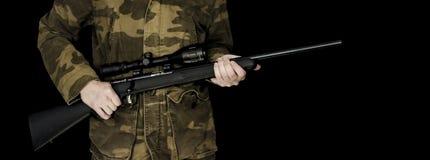 Hombre que sostiene el rifle aislado en negro Foto de archivo libre de regalías