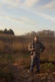 Hombre que sostiene el rifle en campos Imagenes de archivo