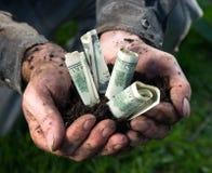 Hombre que sostiene el suelo con los dólares Imagen de archivo