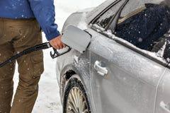 Hombre que sostiene el surtidor de gasolina, depósito de gasolina de relleno del coche cubierto con nieve en invierno imágenes de archivo libres de regalías
