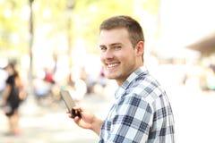 Hombre que sostiene el teléfono móvil que le mira Imágenes de archivo libres de regalías