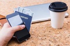 Hombre que sostiene el teléfono y el pasaporte imagenes de archivo