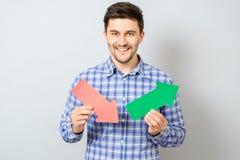 Hombre que sostiene flechas con el gráfico de levantamiento Imágenes de archivo libres de regalías