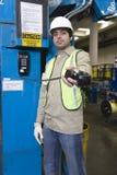 Hombre que sostiene hacia fuera el receptor de teléfono en fábrica Imagen de archivo libre de regalías