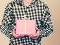 Hombre que sostiene la actual caja de regalo rosada Fotos de archivo libres de regalías