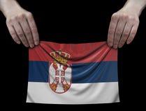 Hombre que sostiene la bandera servia Imagen de archivo libre de regalías