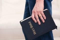 Hombre que sostiene la biblia a su lado Fotos de archivo