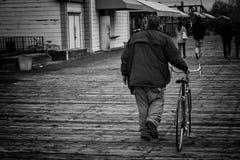 Hombre que sostiene la bici Foto de archivo