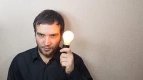 Hombre que sostiene la bombilla Imagen de archivo