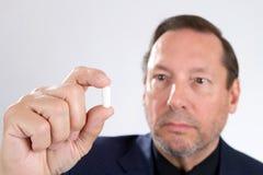 Hombre que sostiene la cápsula de la píldora Fotos de archivo