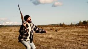 Hombre que sostiene la escopeta Caza de la monta?a El cazador está en un claro del bosque y amontona su escopeta en botín almacen de video