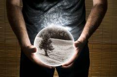Hombre que sostiene la esfera blanca con la imagen del paisaje de la sepia dentro Imagen de archivo libre de regalías