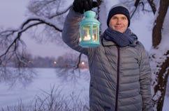 Hombre que sostiene la linterna con la vela al aire libre Fotografía de archivo libre de regalías