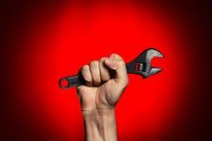 Hombre que sostiene la llave ajustable sobre rojo Imagenes de archivo
