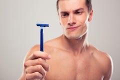 Hombre que sostiene la maquinilla de afeitar Fotos de archivo
