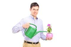 Hombre que sostiene la planta y una regadera Fotos de archivo libres de regalías