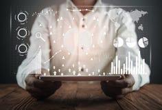 Hombre que sostiene la tableta de Digitaces Estadísticas financieras, gráficos de negocio, red social y conexión Futuro y concept imagen de archivo libre de regalías
