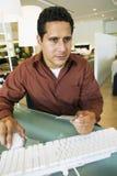 Hombre que sostiene la tarjeta de crédito mientras que usa el ordenador en tienda fotos de archivo libres de regalías