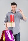 Hombre que sostiene las cajas del bagsand con la tarjeta de débito del crédito Imágenes de archivo libres de regalías